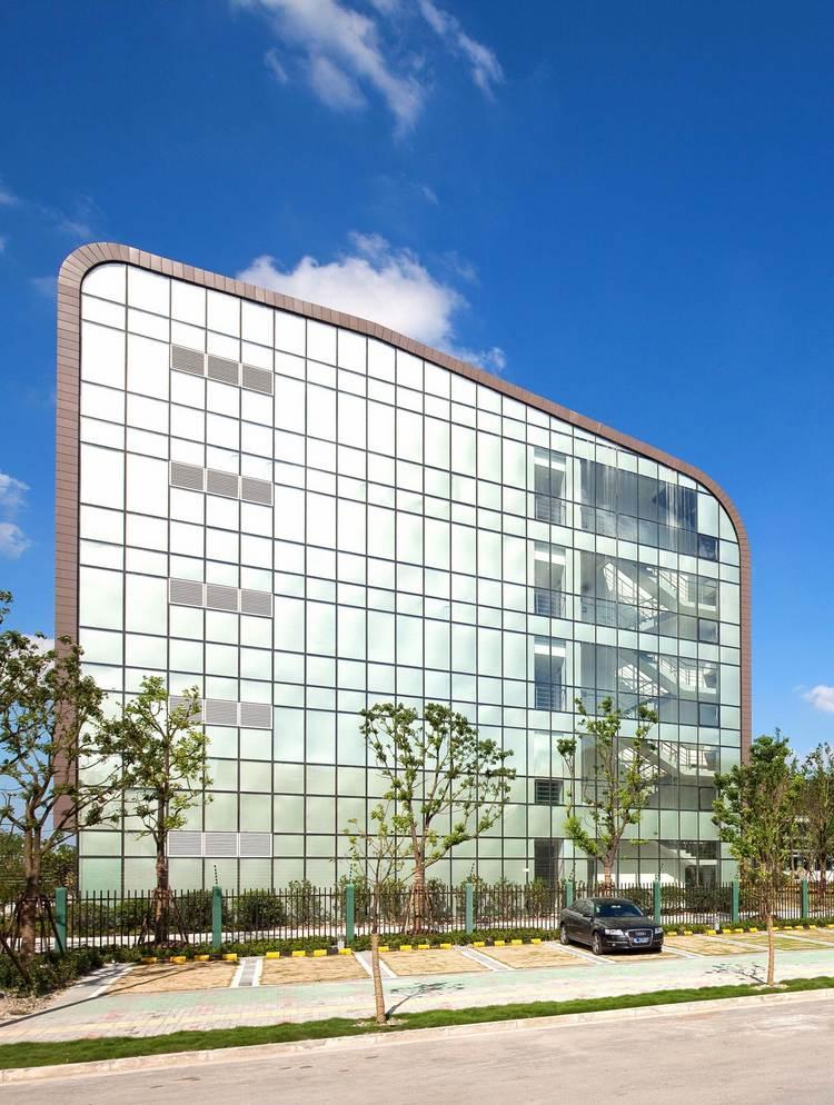 综合体被划分为三个构造带。办公空间(50 000)被容纳在一个矩形体量中,入口大厅将其切分为五部分;中央体量为用于举办活动和展览的服务中心(4 500)、体育中心(3 500)和西面的数据中心(10 000);第三个为一系列的小型建筑,有机布局在公园区(紧邻南侧河流),包含了会议中心和入口广场旁边的酒店大楼(12 5000),以及三座用于培训和科研的大楼(5 500)。